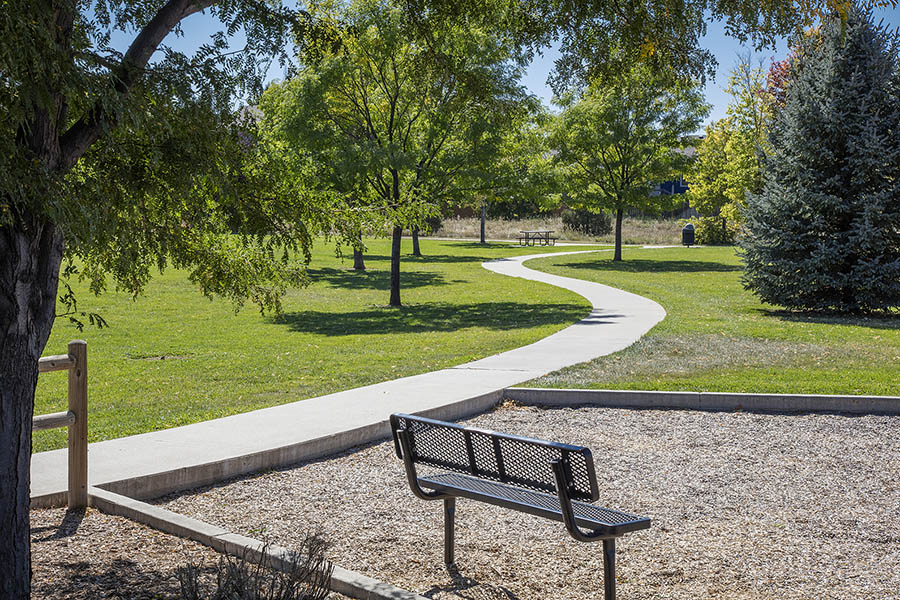 Park with paved sidewalks, grassy areas with tall trees, and bench in mulch.