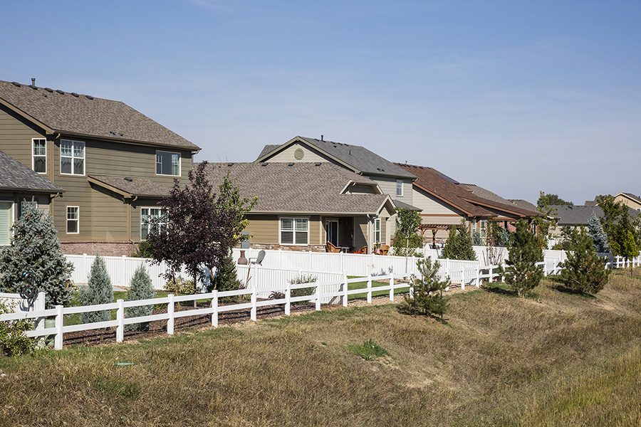 Longmont neighborhood with two story houses and backyards facing open space.