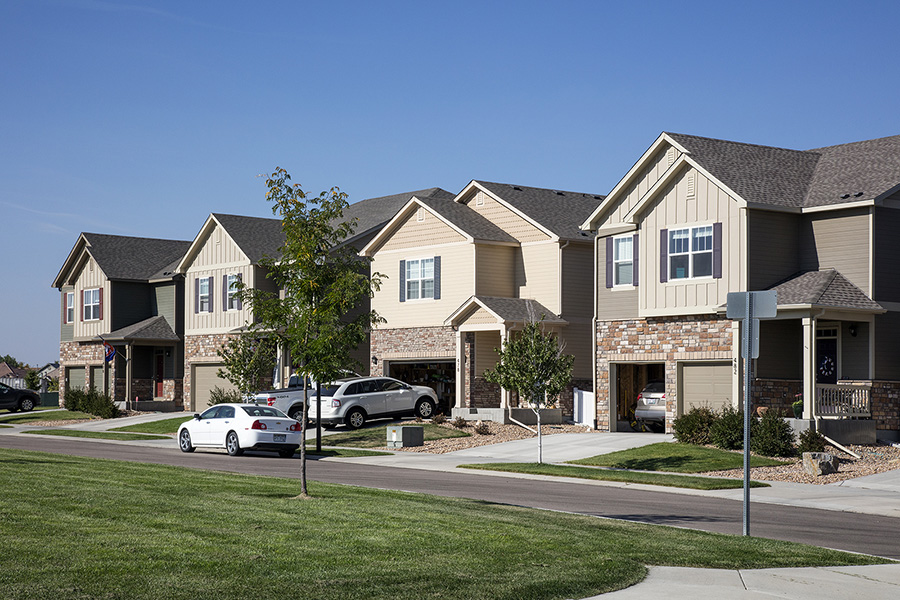 Longmont neighborhood with paved sidewalks, lush landscaping, and two story houses with garages.