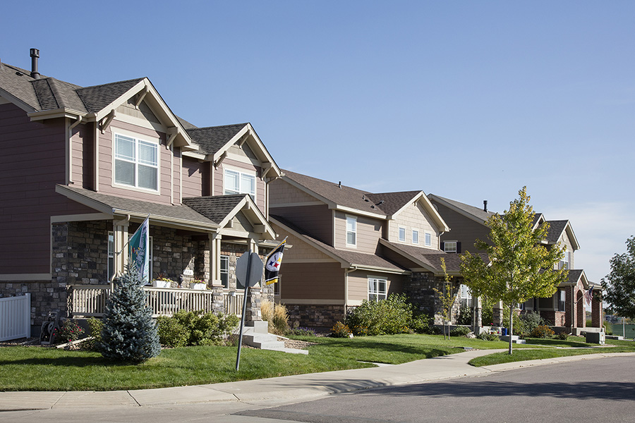 Longmont neighborhood with paved sidewalks, lush landscaping, and two story houses with flags.
