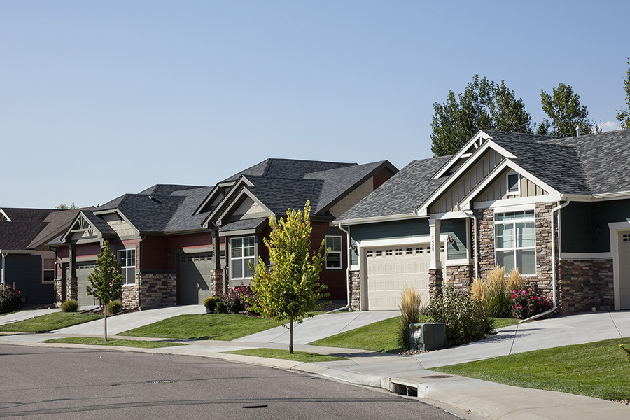 Longmont neighborhood with paved sidewalks, lush landscaping with trees, and two story houses.