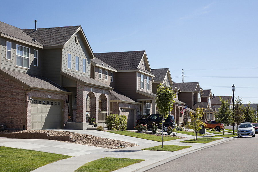 Longmont neighborhood with paved sidewalks, lush landscaping, and two story houses with parked cars.