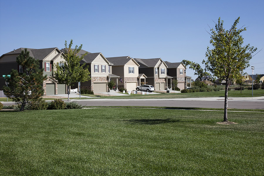 Longmont neighborhood with paved sidewalks, large grassy area with trees, and two story houses.