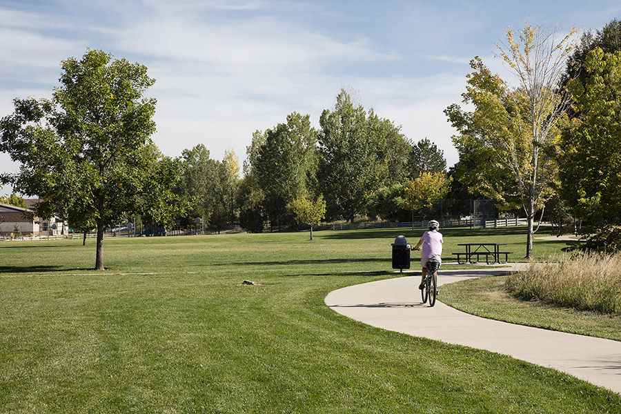 Person riding bike along paved sidewalk in park with grassy areas and tall trees.