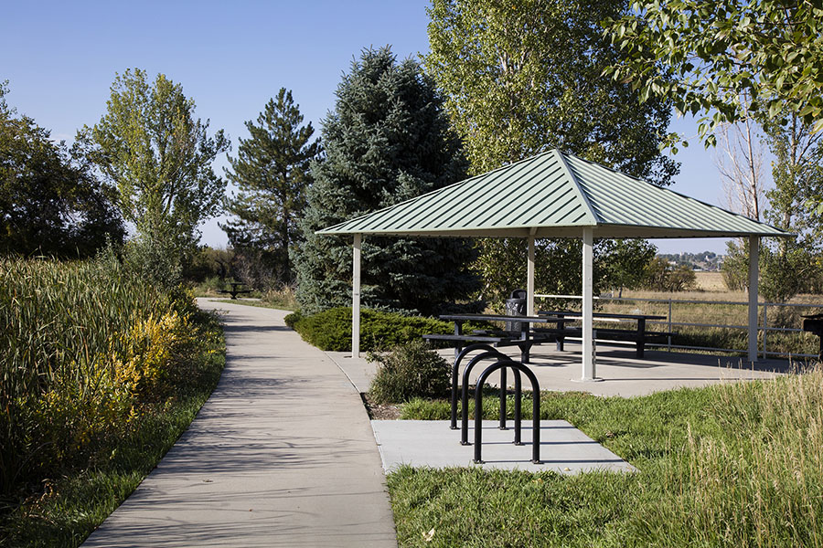 Park with wide paved walkways, bike rack, grassy areas with tall trees, and gazebo with picnic tables.