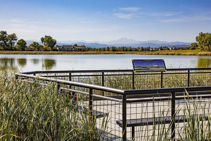 Lake with grass shoreline, pier with educational sign, and distant misty mountains.