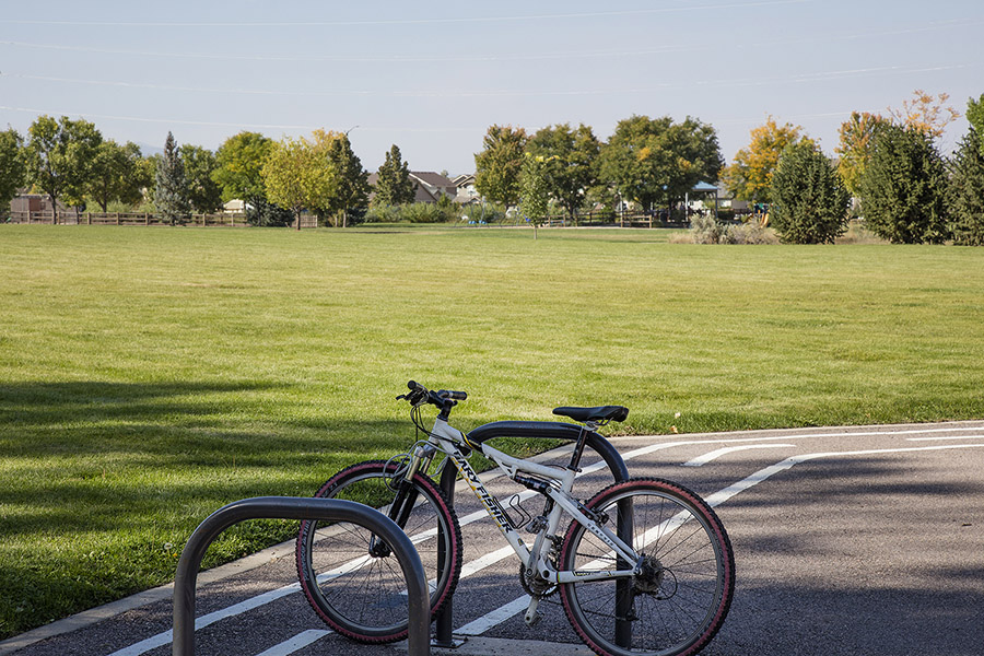 Park with large grassy area, bike rack with bike, and distant trees.