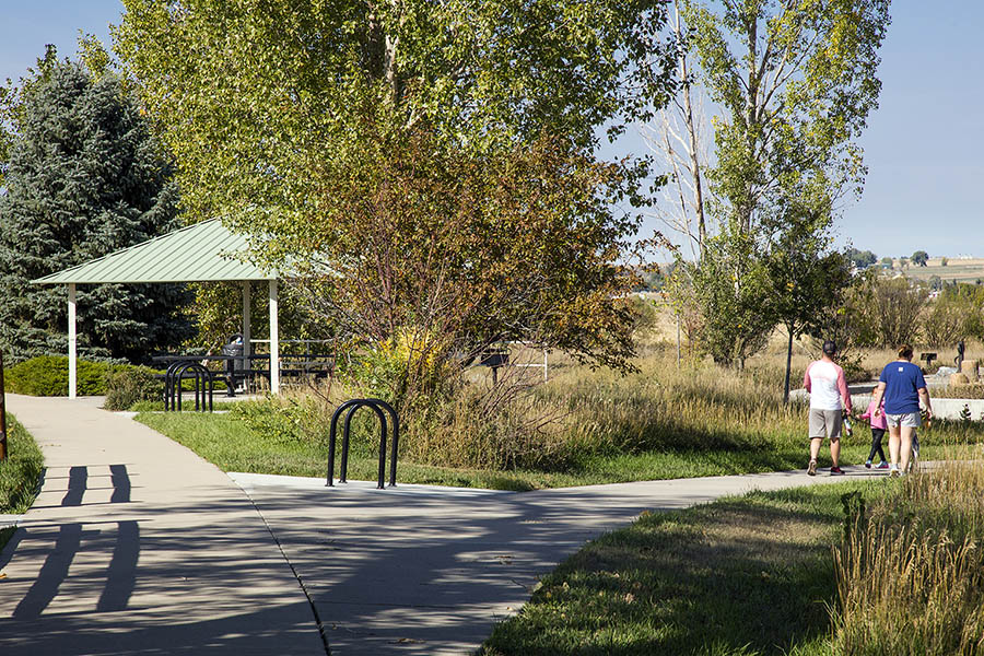 Park with wide concrete paths, grassy areas with tall trees, and gazebo with picnic tables.