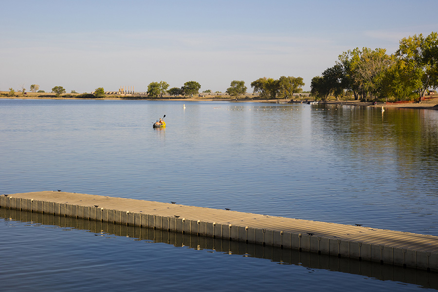 Lake with smooth blue water, concrete dock, and people boating near tree lined shore.