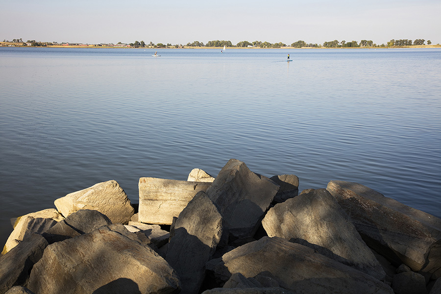 Lake with large rocks in foreground, people boating and paddleboarding, and distant shoreline with trees.