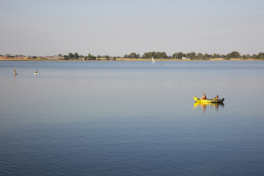 Lake with smooth blue water, distant treelined shore, and people boating and paddleboarding.