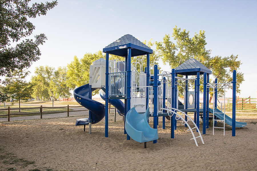 Playground with large play equipment, climbing bars and slides set in sandy play area surrounded by tall trees.