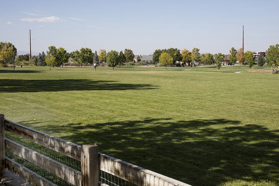 Park with large grassy field, wood fence, and distant trees.