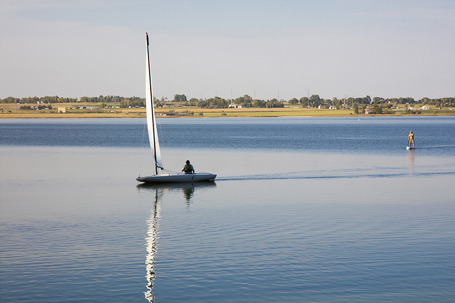 Lake with smooth blue water, distant shoreline with trees and houses, and people boating and paddleboarding.