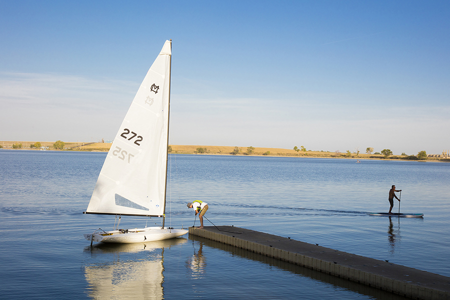 Lake with smooth blue water, man tending to sailboat on dock, and distant shoreline dotted with trees.
