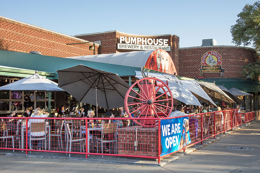 Pumphouse Brewery with large outdoor patio, brick building with garage doors, and decorative red pump outside.