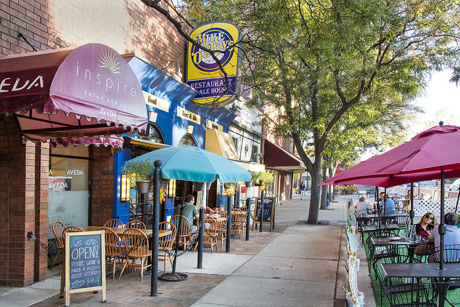 Longmont main street with wide treelined sidewalk, outdoor dining, and shops with large hanging signs.
