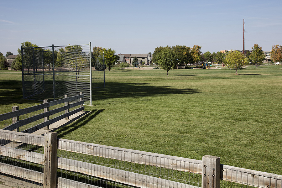 Park with large grassy areas with trees and fenced baseball backstop.