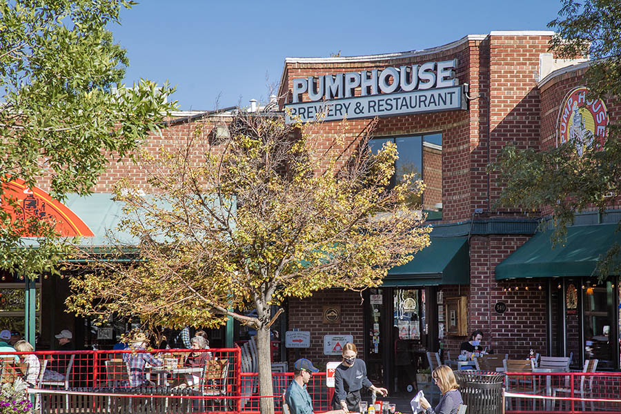Pumphouse Brewery with signage on brick building, outdoor patio with seating, and large leafy trees.