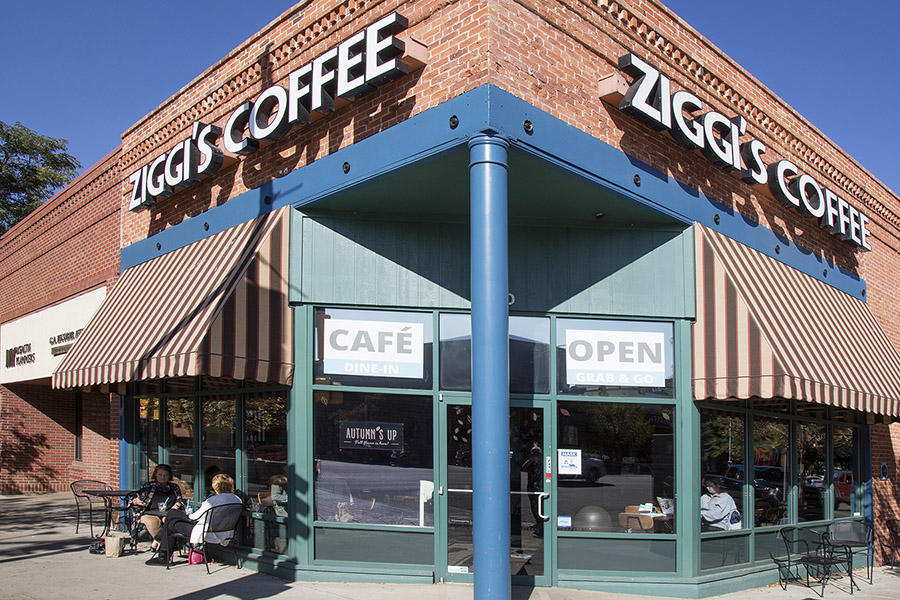 Entrance to Ziggi's Coffee with large glass doors, corner pillar, and striped awnings.