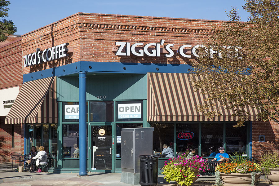 Ziggi's Coffee on the corner of brick building with outdoor seating and striped awnings.