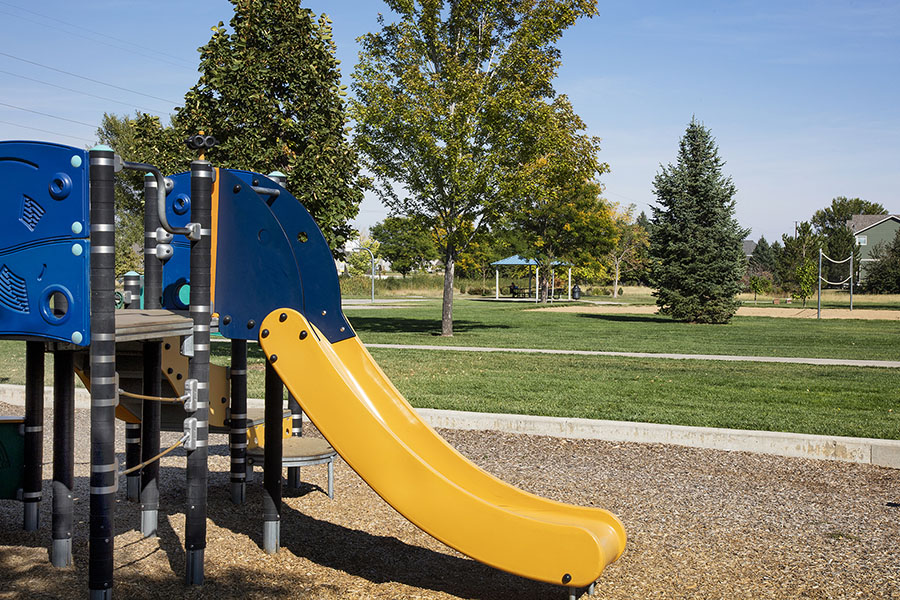 Park with play equipment, slide, grassy areas with trees, and paved sidewalks.