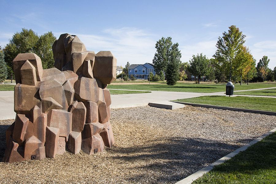 Park with children's climbing wall in mulch, wide paved sidewalks, and grassy areas with tall trees.