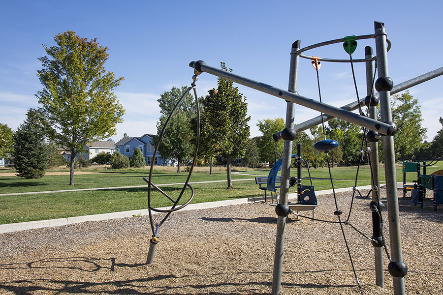 Park with metal play equipment in mulch, grassy areas with tall trees, and paved sidewalks.