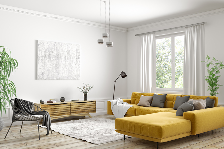 Apartment living room with wood floor, plsuh rug, fabric sectional couch, modern furniture and large windows.
